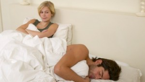 Sleeping man and frustrated woman in bed