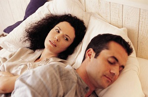 Unhappy woman and sleeping man lying in bed