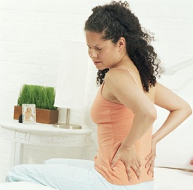 Woman sitting on bed holding back in pain
