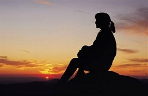 Silhouette of woman sitting at sunset
