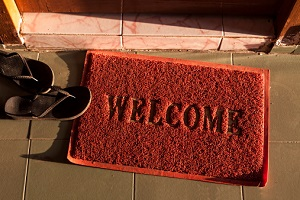 A red welcome doormat sits on a porch with a flip-flop laying on its edge.