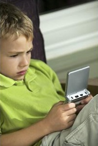 A boy sits in a chair playing a Gameboy with total concentration showing on his face.