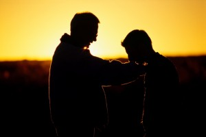 Silhouette of two men talking