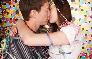 Young couple kissing covered in streamers