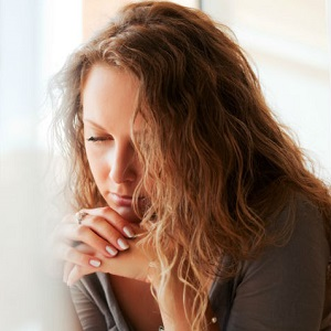 A woman rests her chin on her hands, looking sad and deep in thought.