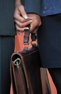 Close up of business people holding hands and brief case