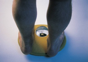 A person's lower legs and feet are shown standing on a scale.