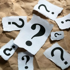 Papers with different sized question marks lay scattered on a table.