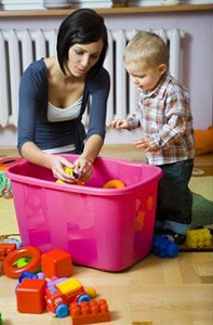 Mother and toddler putting away toys