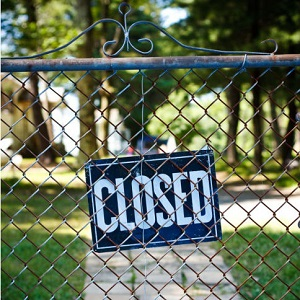 A wire fence is shut and has a closed sign on it.