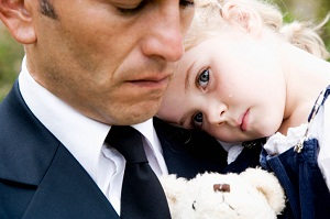 Grieving father holding young daughter