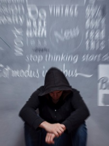 young-man-sits-near-blurry-chalkboard