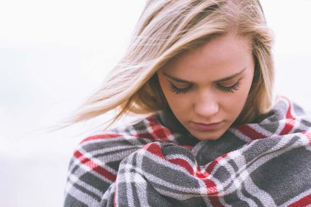 Close up of a young woman covered with blanket
