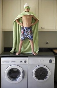 Boy with sheet cape standing on washing machine