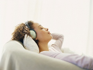 Woman laying down while wearing headphones