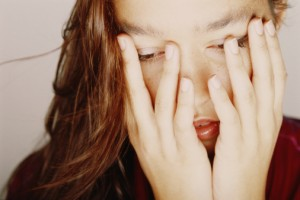 Woman covering face with hands, looking down