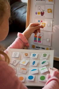 Young girl putting stickers on a board