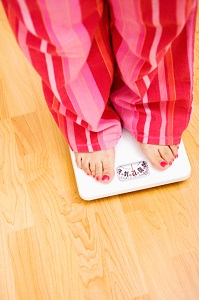 Woman in pajamas standing on scale