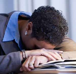 Stressed woman placing her head on her desk