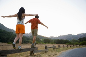 man-and-woman-balancing-while-walking-on-fence