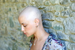 woman with shaved head looking sad