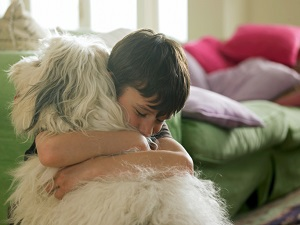 young boy hugging his dog