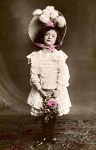 Young girl in frilly dress and flowered hat