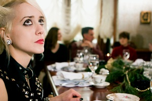young woman looking anxious at holiday dinner