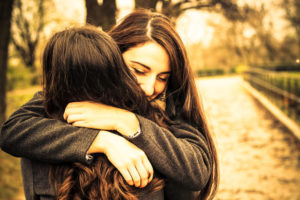 Gold-toned photo of two young adults with long hair hugging in park