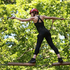Young woman climbing in adventure rope park