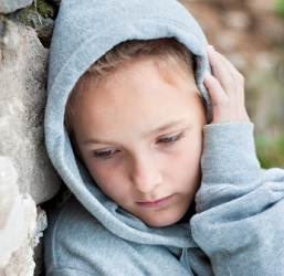 Unhappy, solitary child leans against brick wall