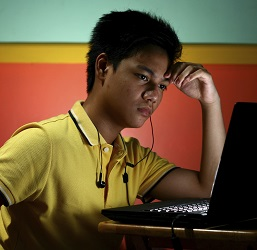A worried teen looks at his computer
