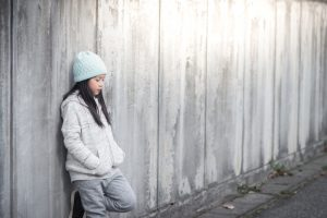 Preteen with long hair under light blue hat stands leaning back against fence, looking thoughtful