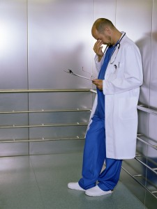 Doctor experiencing compassion fatigue in an elevator.