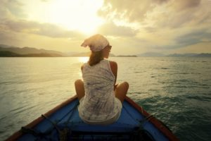 A woman travelling by boat at sunset