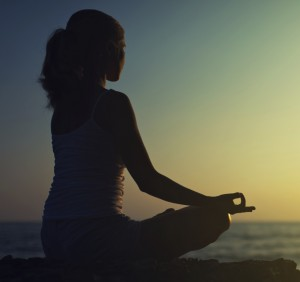 yoga outdoors. silhouette of a woman sitting in lotus position