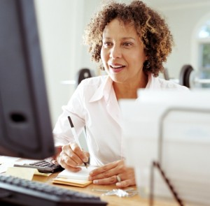 A woman takes notes at her computer