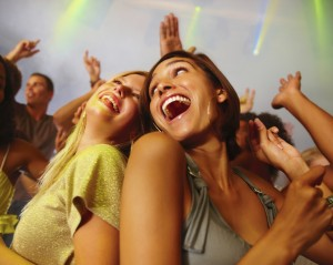 Happy extroverted women dancing at the nightclub.