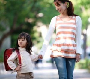 Girl with backpack holding mother's hand, differential focus
