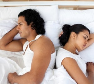 Upset couple in bed sleeping separately