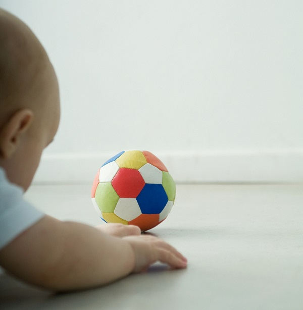A baby looks at a colorful ball