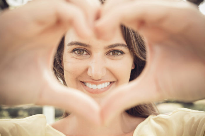 young woman making heart sign
