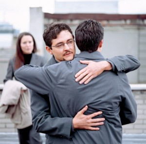 close-up of two men hugging with a woman standing behind them