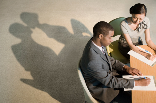 Shadows of two office workers show affection
