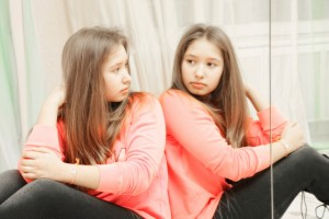 Teenage girl looking at her reflection closeup