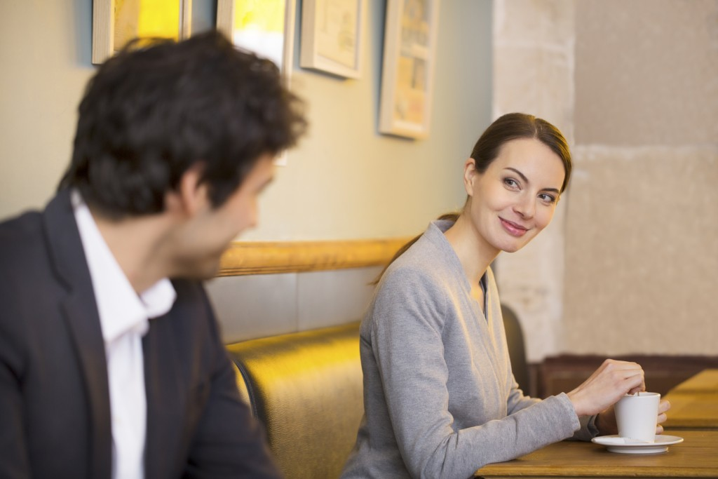 A woman flirts with a man in a cafe