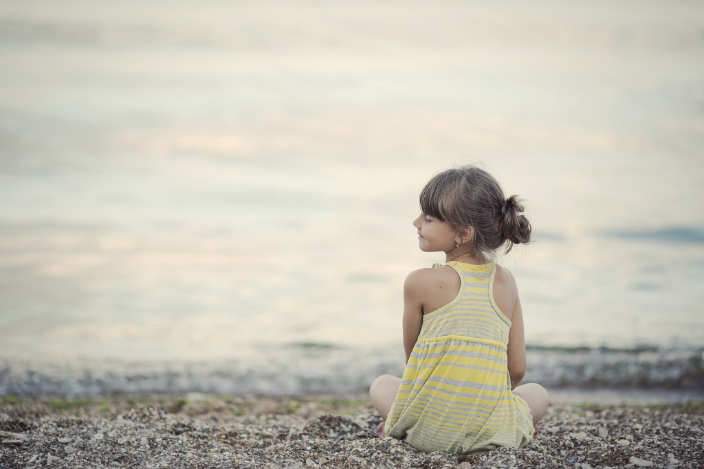 A calm child sits at the water's edge