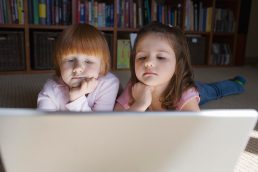 Young girls (5-6) lying on floor using laptop,  contemplating with hand on chin