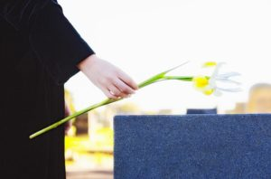 Woman's hand leaving flower on tombstone