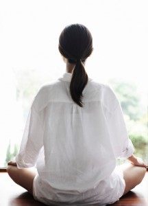 Meditating woman facing away from the camera